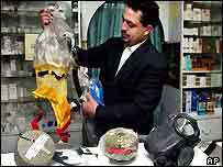 Yussef Abdel Hamid al-Mimi shows different types of gas masks at a pharmacy in the West Bank city of Ramallah
