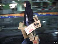 An Israeli Arab woman leaves a gas mask distribution centre with several gas mask kits at a mall in Jerusalem