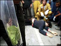 Thai police stand over the body of a victim