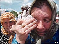 Bosnian Muslim women cry as they attend the memorial service for Srebrenica victims