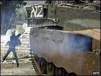 A Palestinian throws stones at a tank in Nablus