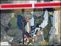 Israeli soldiers look for evidence at the Kiryat Arba settlement