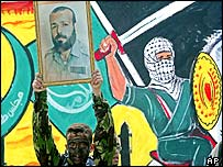 A Hamas militant holds up a portrait of Maqadma in front of a mural