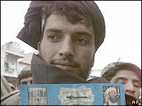 Man holding pamphlet offering money for information on Bin Laden on the Pakistan-Afghanistan border
