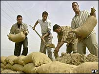 Iraqi workers dig trenches and fill sandbags to make bunkers in the event of a US- led war on Iraq