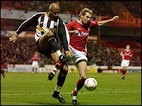 Grimsby's Georges Santos and Darren Huckerby battle for the ball