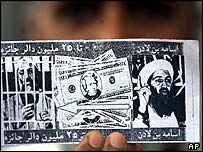 Pakistani man holds a US leaflet offering a reward for the capture of Osama Bin Laden