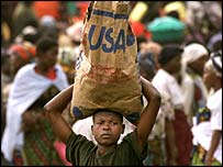 A man carries food aid back from a distribution centre in the eastern DRC