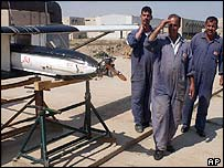 Iraqi workers in front of what Baghdad says is a prototype of a drone which the US claims can deliver chemical weapons