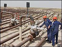Oil workers at a crude oil flowline in Maqwa Oil Field, Kuwait