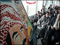 Ceremony to award cheques under a painting of Arafat and Saddam