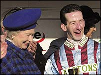 Best Mate's jockey Jim Culloty receives his trophy from the Queen