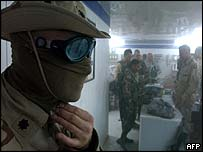 Lieutenant Colonel Octavio Mont from the Combat Support Hospital covers his face as dust penetrates the US military grocery during a sandstorm