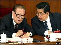 Jiang Zemin (left) listens to Hu Jintao