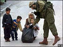 An Israeli soldier checks a Palestinian woman's plastic bag