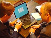 Businessmen around a laptop