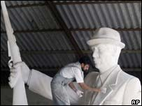 A worker puts the finishing touches to a statue of Saddam Hussein