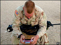 A US soldier plays a computer game while waiting in Kuwait.