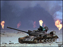 Burnt out tank and burning oil wells in 1991 Gulf War