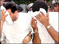 Two defendants at the retrial last year hide their faces as they enter court