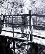A.A. Milne standing on the original pooh-sticks bridge in Ashdown Forest