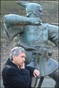 Ali Asghar talks on mobile phone at the Robin Hood statue
