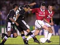 Edmundo of Vasco shoots past Denis Irwin of Manchester during the Vasco da Gama v Manchester United World Club Championship Group