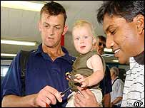 Adam Gilchrist carrying his son