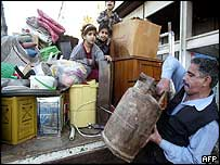 A Baghdad family load supplies onto a truck