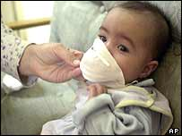 A Baghdad mother tests a gauze mask on her baby