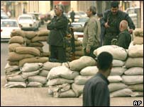 Iraqi Baath party volunteers stand guard at a sandbag position on Sadoun Street in downtown Baghdad