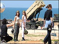 Israeli models pose in front of US Patriot missiles