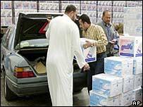 Kuwaiti man loads bottled water into his car
