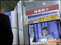 Taiwanese pedestrian watches news, AP