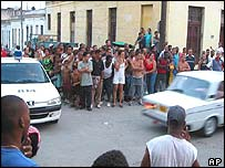 People look on as Cuban dissident Raul Rivero is driven away