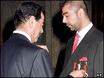 Saddam Hussein with his son Uday (right)