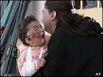 A mother tries to comfort her injured child outside a Baghdad hospital