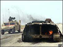 US troops pass burnt out Iraqi personnel carrier near Basra