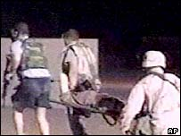 Soldiers carry one of those injured in the attack (CBS TV image)