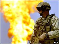 A US marine in front of a burning oil well