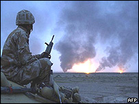 British soldier watching oil wells on fire in Southern. Iraq