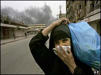 A women in Baghdad covers her face against smoke from Iraqi defences