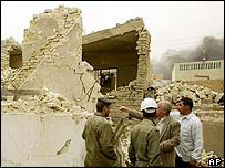 Men in Baghdad examine a house reportedly destroyed by a missile