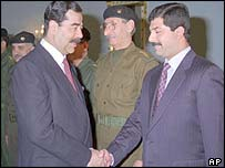 Saddam Hussein, left, with son Qusay