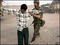 A British soldier with the 1st Armoured Division stops and searches an Iraqi man Monday