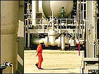 An Indian oil worker walks through a refinery