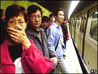 Passengers waiting to get on a train at a Hong Kong underground station covers her mouth and nose