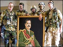 UK soldiers pose with picture of Saddam Hussein