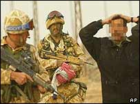 Royal Marines guard an Iraqi prisoner