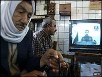 Iraqi people watch a TV address by Saddam Hussein on Monday